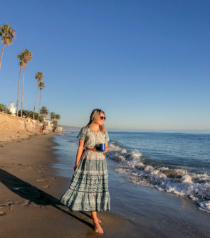 Jessica Sturdy wearing a blue printed Sea New York dress on Butterfly Beach in Santa Barbara, California at sunset.