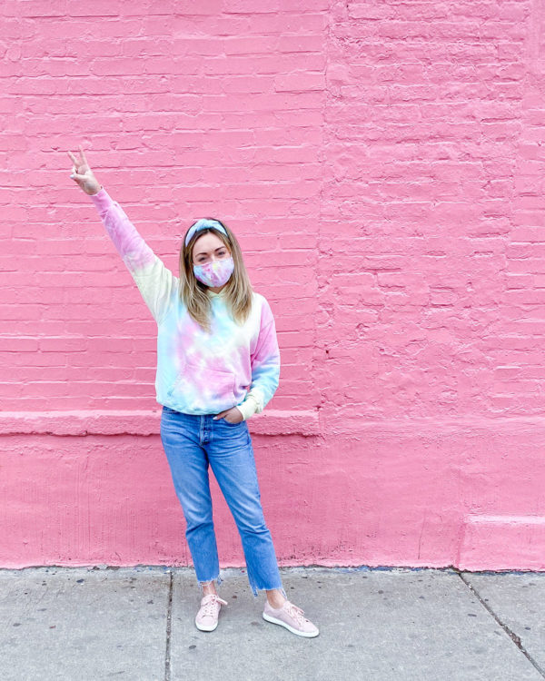 Chicago blogger Jessica Sturdy of Bows & Sequins wearing a tie dye Lele Sadoughi headband, a Dannijo tie dye sweatshirt, a tie dye face mask, cropped raw hem jeans, and pink sneakers.