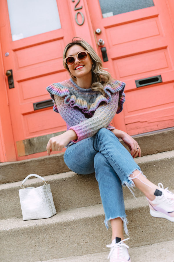 Chicago fashion blogger Jessica Sturdy that writes the blog Bows & Sequins wearing a rainbow ruffle sweater from LoveShackFancy with raw hem jeans and pastel sneakers in front of a coral door on Damen in Bucktown.