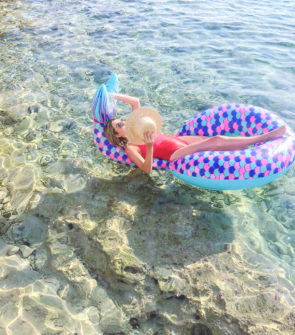 Jessica Sturdy wearing a Summersalt swimsuit floating on a mermaid tail pool float in the clear water off of the Palisinki Islands in Hvar Croatia