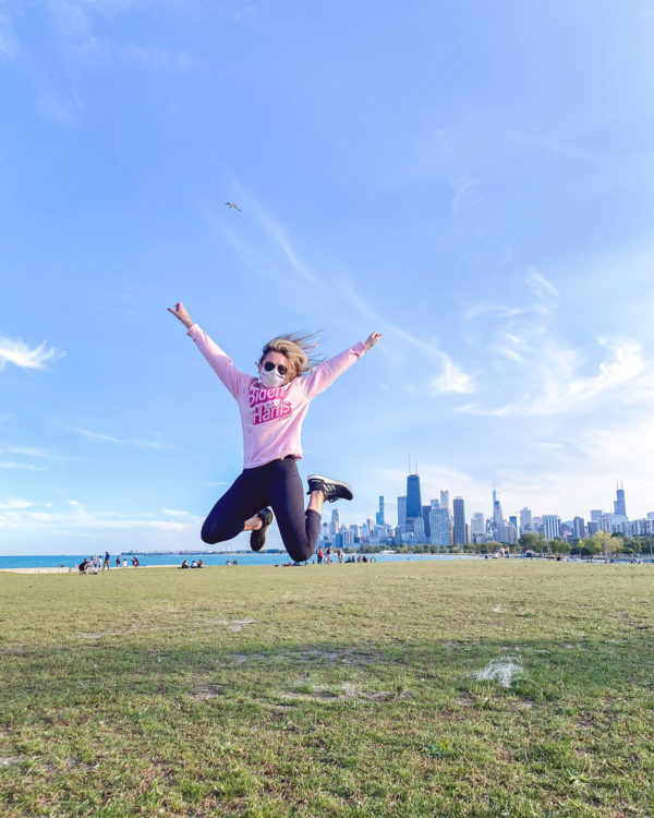 Chicago blogger Jessica Sturdy jumping in front of the skyline wearing a pink Barbie-inspired Biden Harris 2020 sweatshirt with Lululemon Leggings and black Adidas Ultraboosts.