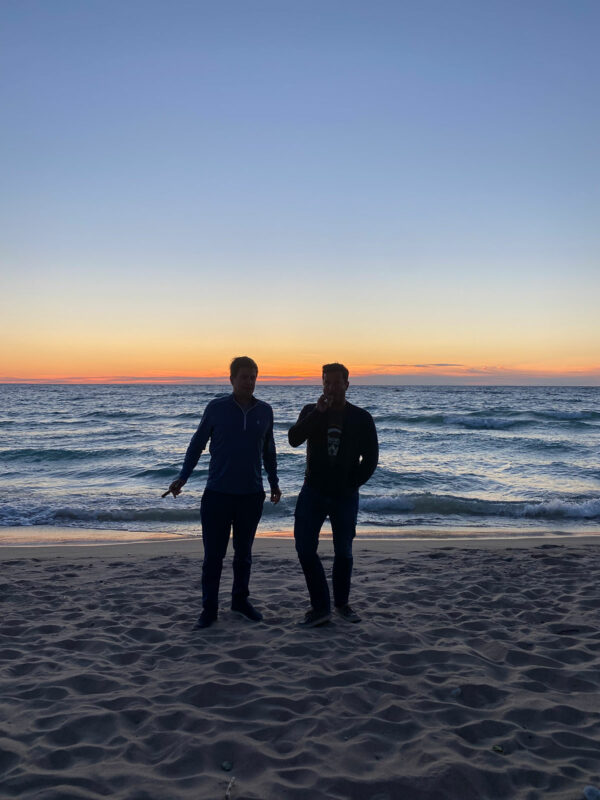 Two guys standing on a beach at sunset smoking cigars