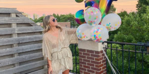 Jessica Sturdy at her Golden Birthday Party wearing a sheer gold sparkly dress by IRO, metallic lace-up sandals by Marc Fisher, and holding rainbow numbers and confetti filled balloons.